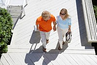 Couple with luggage walking up steps high angle view