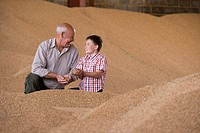 Farmer and grandson cupping wheat grains on grain heap