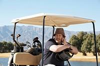 Man talking on phone in golf cart