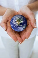 Close up of womanÆs hands cupping miniature globe (thumbnail)