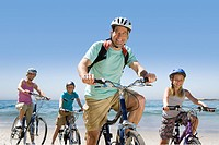 Portrait of family riding bicycles on beach