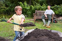 Grandfather watching grandson fill wheelbarrow with dirt