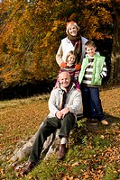 Portrait of grandparents and grandkids in grass with autumn leaves