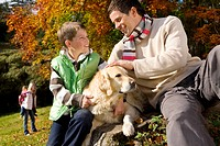 Father, son, and dog sitting on tree stump in woods