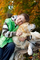 Portrait of boy hugging dog on tree stump