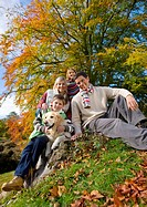 Portrait of family and dog sitting on tree stump in woods (thumbnail)