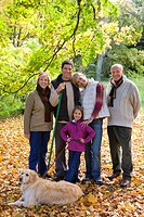 Portrait of multi_generation family and dog standing in autumn leaves
