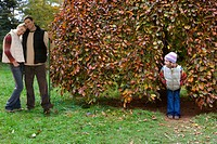 Boy peering at girl hiding in tree
