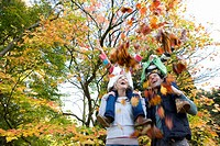 Kids on parentsÆ shoulders throwing leaves