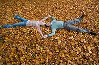 Couple holding hands and laying in autumn leaves