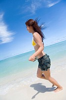 Young woman running on beach, smiling, blurred motion, Saipan, USA