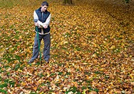 Man with rake standing in autumn leaves