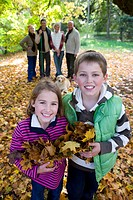 Portrait of boy and girl holding autumn leaves with family in background