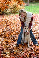 Portrait of woman and dog standing in autumn leaves