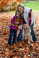 Mother, daughter, and dog standing in autumn leaves