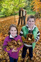 Portrait of boy and girl holding autumn leaves with parents in background
