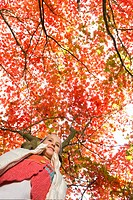 Girl standing under tree with autumn leaves