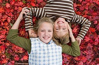 Portrait of brother and sister laying in autumn leaves