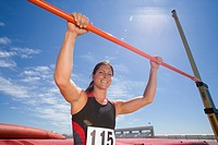 Young female athlete with hands on bar, low angle view lens flare