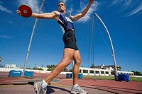 Male athlete preparing to throw discus, low angle view