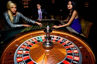 Man flanked by women, gambling at roulette table, portrait (thumbnail)