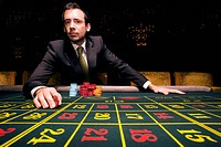Man gambling at roulette table, portrait, low angle view