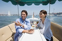 Young adult couple on a cruiser having wine, Side View