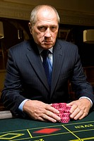 Mature man with gambling chips at roulette table, portrait