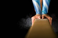Female gymnast performing on balance beam, close_up of hands