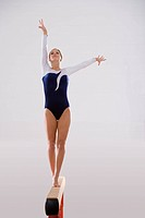 Female gymnast performing on balance beam, portrait, low angle view (thumbnail)