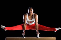 Male gymnast performing on pommel horse, portrait, low angle view (thumbnail)