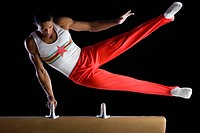 Male gymnast performing on pommel horse, low angle view
