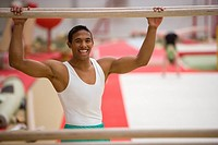 Male gymnast with hands on parallel bars, smiling, portrait