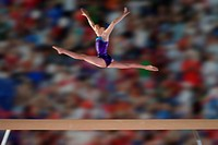 Young female 10_12 gymnast performing splits in air above balance beam, side view