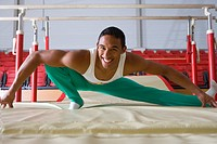 Male gymnast stretching in gymnasium, smiling, portrait