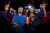 Couple in cinema wearing 3D glasses, smiling, low angle view