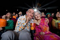 Senior couple sharing drink in cinema, low angle view (thumbnail)