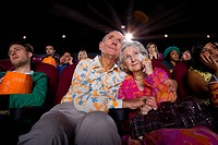 Senior couple in cinema, man with arms around woman, low angle view