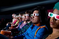 Audience in cinema wearing 3D glasses, side view