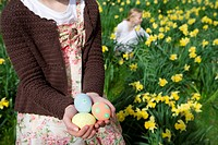 Young girl holding decorated Easter eggs (thumbnail)