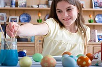 Young girl decorating Easter eggs