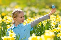 Young girl holding decorated Easter egg in field of daffodils