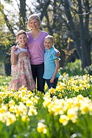 Mother and daughters standing in field of daffodils