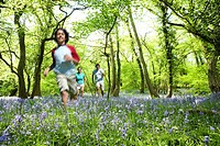 Boy running through field of bluebell flowers