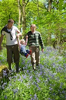 Couple swinging child over field of bluebell flowers