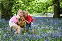 Children and dog posing in field of bluebell flowers
