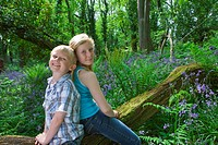 Children sitting on log among bluebell flowers