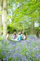 Children sitting in field of bluebell flowers