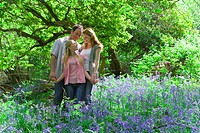 Family standing in field of bluebell flowers
