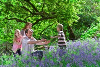 Family playing in field of bluebell flowers